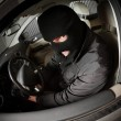 Stock Photo: Robber and the thief in a mask hijacks the car