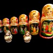 Stock Photo: Eight sets of nesting dolls on black