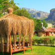 Summerhouse covered straw and tall mountains. — Foto Stock