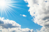 Grey clouds and pretty sun high in the sky. — Stock Photo