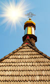 Wonderful sunrise and old roof of church. — Stock Photo
