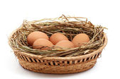 Chicken eggs and hay in the brown basket . — Stock Photo