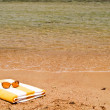 Sunglasses and towel next to the sea. - Stock Photo