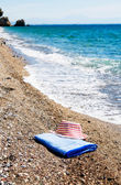 Turquoise sea,sun hat and towel. — Stock Photo