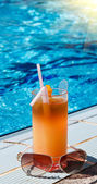 Sunglass and tasty cocktail with lemon next to swimming pool. — Stock Photo