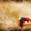 Wonderful basket full of autumn fruits on a grunge background — Stock Photo