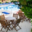 Stock Photo: Hotel patio with tables and chairs next to swimming pool.