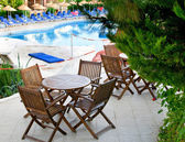 Hotel patio with tables and chairs next to swimming pool. — Stock Photo