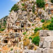 Ancient tombs in the rock high  mountains and fun sun on the sky — Stock Photo