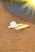 Turquoise sea,sunhat and towel. — Stock Photo