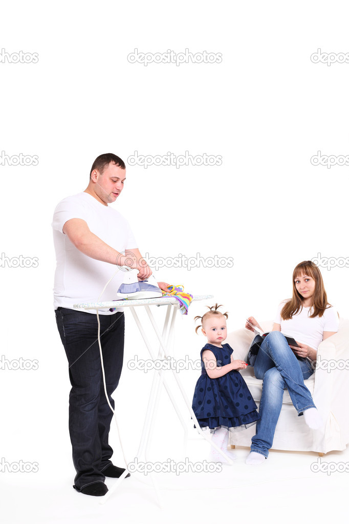 Family efforts.  husband irons clothes.  wife has a rest, sitting in an armchair. — Stock Photo #5680270
