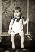 Little girl in a dress in sailor's style sits on a rope swing. — Stock Photo