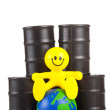 Toy smiling little man sits next on butts to oil the globe. — Stock Photo