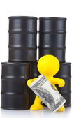 Toy little man costs at butts with oil and holds many money. — Stock Photo