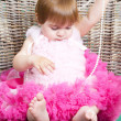 Little girl in an elegant dress sits in a wicker chair — Stock Photo #5861192