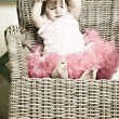 Little girl in an elegant dress sits in a wicker chair — Stock Photo #5861193