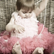Little girl in an elegant dress sits in a wicker chair — Stock Photo #5861194