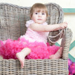 Little girl in an elegant dress sits in a wicker chair — Stock Photo #5861195