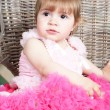 Little girl in an elegant dress sits in a wicker chair — Stock Photo #5861197