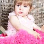 Little girl in an elegant dress sits in a wicker chair — Stock Photo