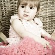 Little girl in an elegant dress sits in a wicker chair — Stock Photo #5861199