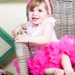 Little girl in an elegant dress sits in a wicker chair — Stock Photo #5861201