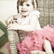Little girl in an elegant dress sits in a wicker chair — Stock Photo #5861203