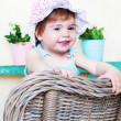 Happy girl in panamke sits in a wicker chair — Stock Photo