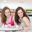 Two friends talk in cafe in shopping center — Stock Photo