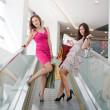 Two friends with purchases on the escalator — Stock Photo
