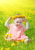 Little girl walks on a glade with dandelions — Stock Photo