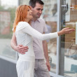 Married couple to stand at a shop show-window. - Stock Photo