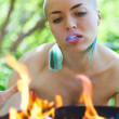 Bald girl spends a ritual ceremony over fire - Stock Photo