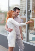 Married couple to stand at a shop show-window. — Stock Photo