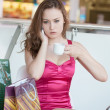 Girl in a pink dress with a mobile phone in shopping center — Stock Photo