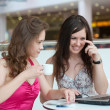 Two girls work on a laptop, sitting in cafe in shopping center — Stock Photo