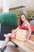 Girl with purchases in the big shopping center — Stock Photo