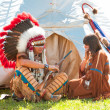Stock Photo: North AmericIndians sit at wigwam