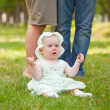 Cheerful baby girl is playing on the grass — Stock Photo