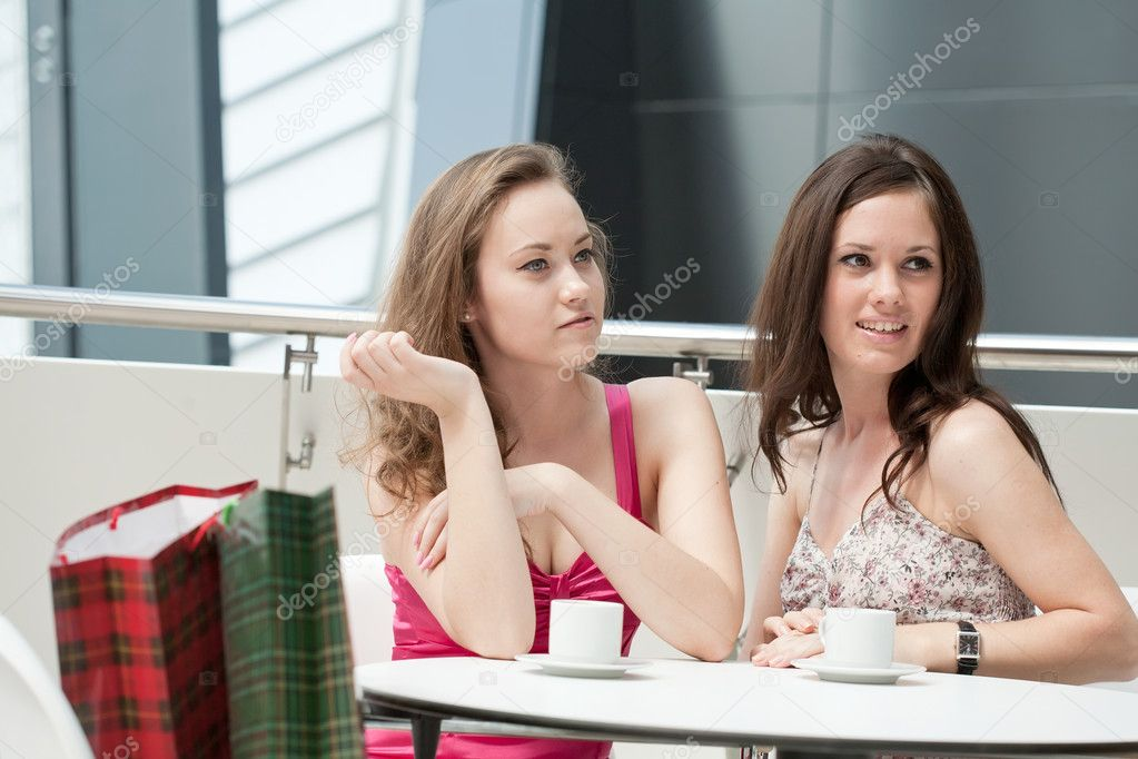 Two girls sitting in cafe in shopping center — Stock Photo #6638704