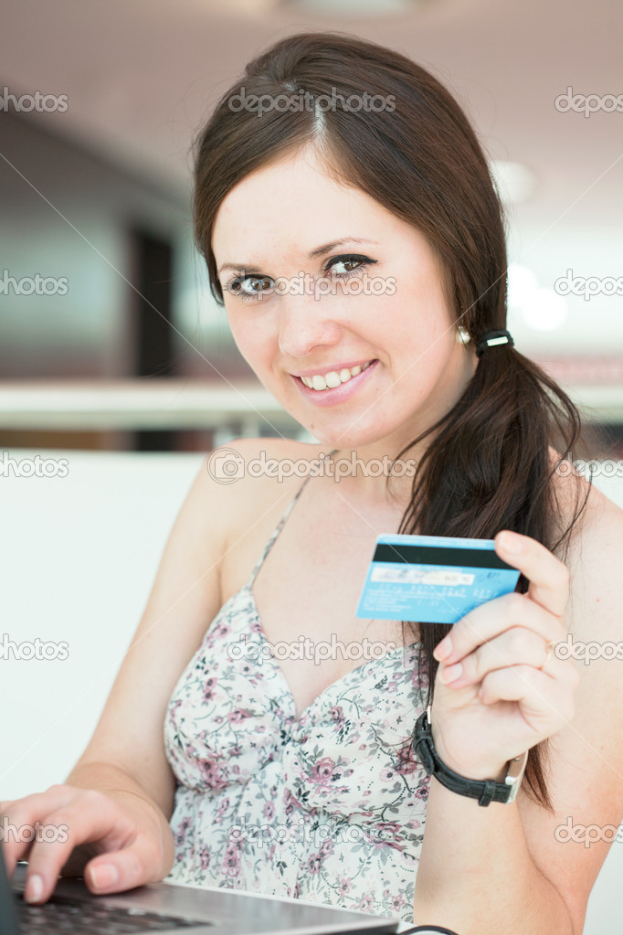 Girl pays purchase through the Internet, sitting in cafe in shopping center — Stock Photo #6638708