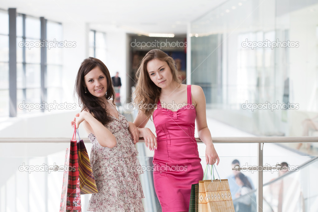 Two friends with purchases in the big shopping center — Stock Photo #6638724