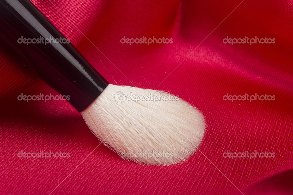 White brush for cosmetics on a red background.  Stock Photo #5396900