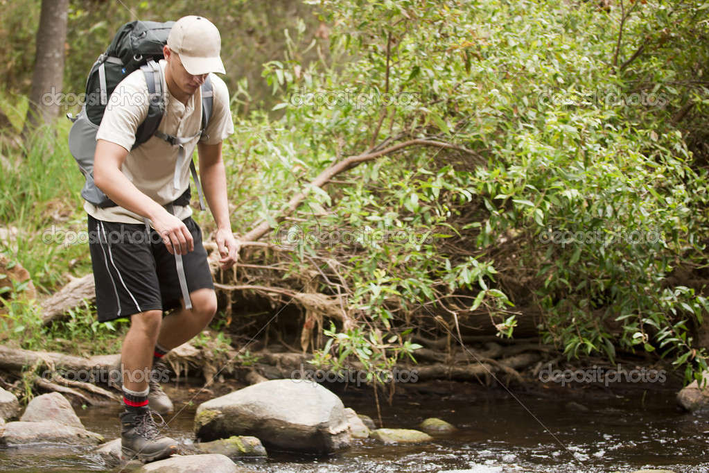 A young male crossing a stream during a hiking trip. — Stock Photo #6403911