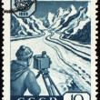 Researcher with device in mountain on post stamp — Stock Photo