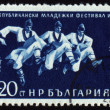 Three dancing men in Bulgarian national costumes on post stamp - Stock Photo