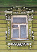 Old wooden window, decorated with carving — Stock Photo