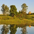 Lake bank with small house - Foto Stock