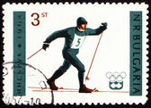 Running skier on post stamp — Stock Photo