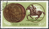 Sportsman riding horse and Olympic medal on post stamp — Stock Photo